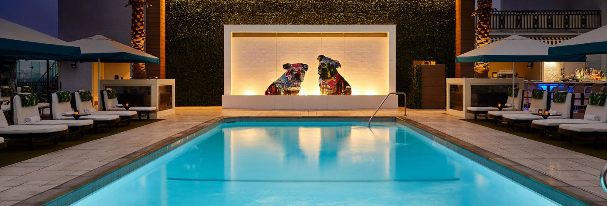 Night time shot of a pool with pug statues at the London West Hollywood