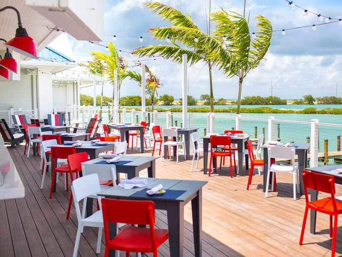 Angler & Ale's outdoor restaurant patio with red and white chairs overlooking the gulf