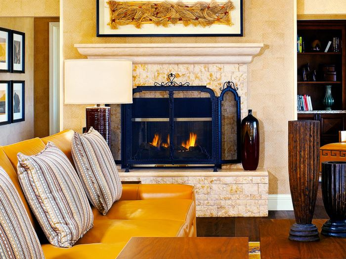 A yellow couch by quaint fireplace in one of the rooms at the JW Marriott Phoenix Desert Ridge Resort & Spa