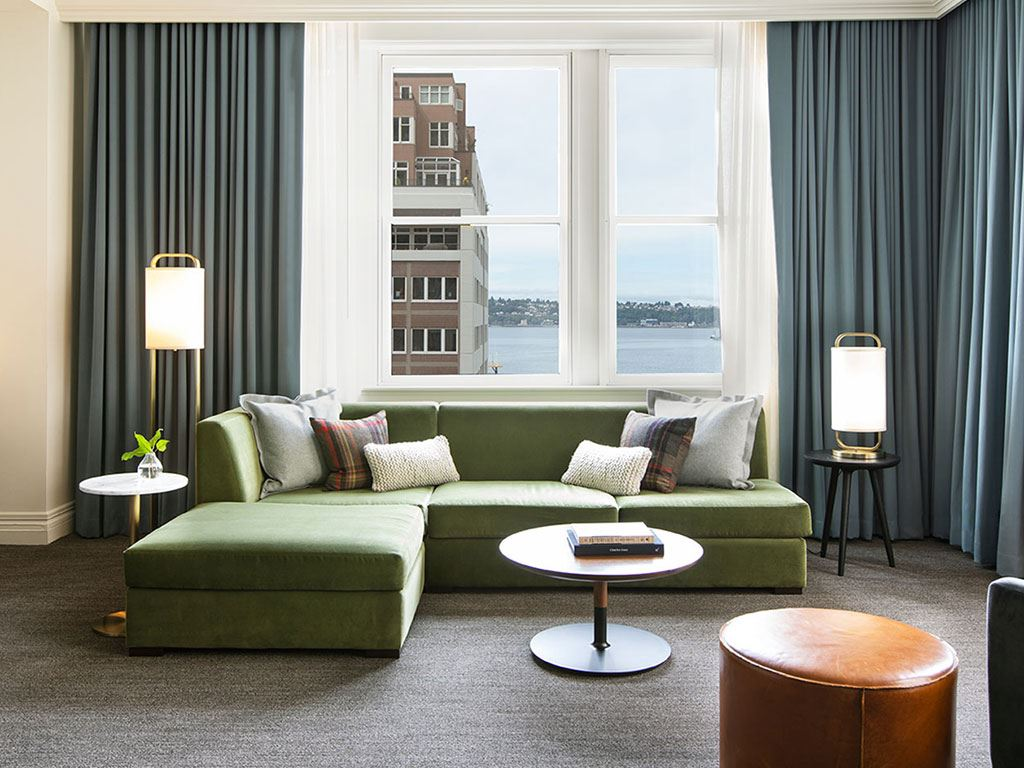 A soft green couch by a window at the Kimpton Alexis Hotel