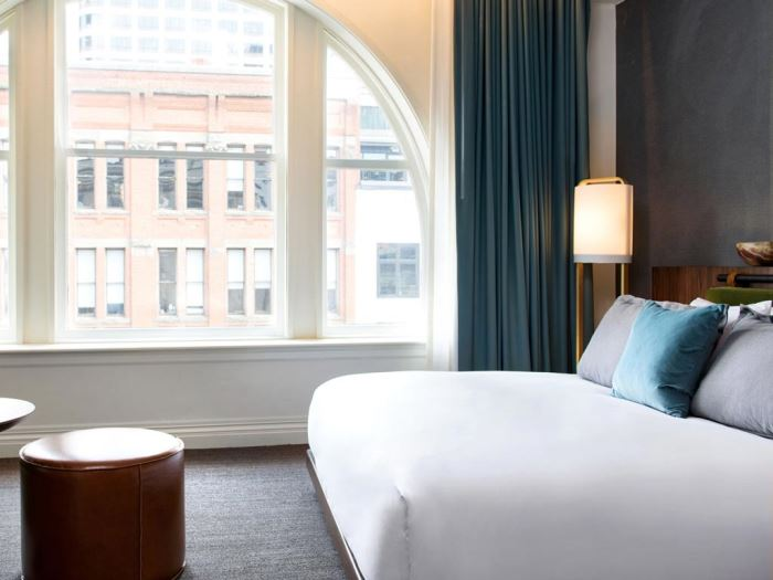 A nice bed by a large window overlooking the city at the Kimpton Alexis Hotel