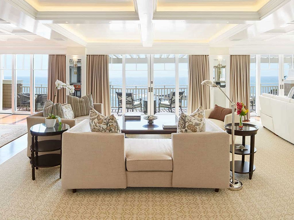 A shot of a white living room interior overlooking the ocean at the Montage Laguna Beach hotel